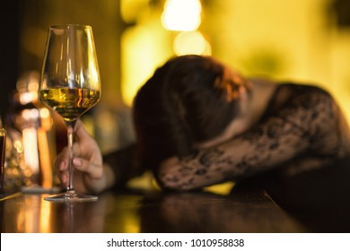 Wasted woman sleeping on the bar counter after drinking too much alcohol selective focus on a glass of wine copyspace booze alcoholic problem addicted addiction lifestyle party event depression