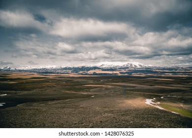 wasteland under the dramatic sky and snowy mountain view
