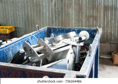 Waster metallic container bin with full with rubbish on factory in workshop. Horizontal colored image.