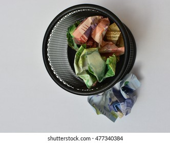 Wasting Money concept; wastepaper basket with crumbled money; throwing money away. Close-up top view isolated on white.