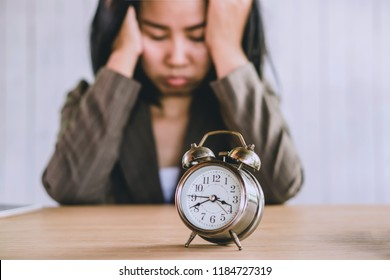 wasting time concept with angry Asian business woman tired and bored waiting for someone coming late at work with alarm clock on desk