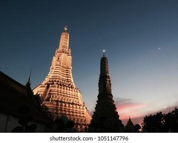 Wat Arun at night, Beautiful golden pagoda with lighting and beautiful sunset sky in the background, Wat Arun Ratchawararam Ratchawaramahawihan is a Buddhist temple in Bangkok, Thailand.
