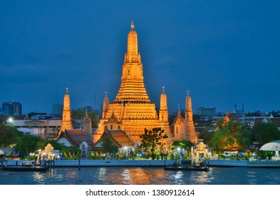 The Wat Arun (Temple of Dawn) illuminated at dusk with the Chao Phraya River in the foreground in Bangkok, Thailand.