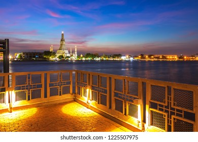 Wat Arun Temple at sunset in bangkok Thailand. Wat Arun is among the best known of Thailand's landmarks. River view terrace overlooking Wat Arun.  River view balcony. copy space