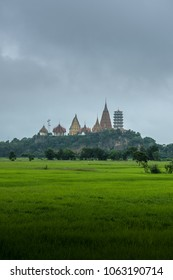 Wat Nongseu (tiger cave) temple with rice field foreground in rainy season, Kanchanaburi, western Thailand