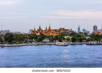 Wat Phra Kaew, Temple of the Emerald Buddha view from Chao Phraya River side after sunset time in Bangkok Thailand, with smooth river.