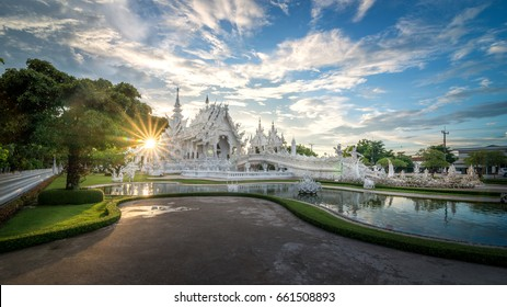 Wat Rong Khun or White temple in Chiang Rai, Thailand in sunset time with a beautiful sky.