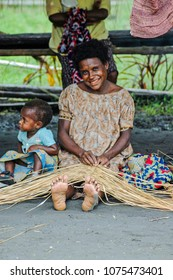 Watam, East Sepik Province/Papua New Guinea, March 20 2009:  A woman sits in the shade of a hut, weaving a basket. Her teeth are stained from chewing betel nut. Her young daughter sits by her side
