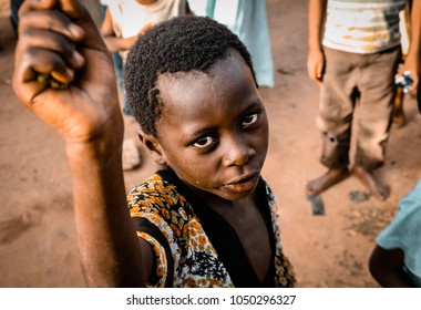 Watamu, Kenya / Africa - 08/10/2016: An African-colored child asks for help as he is portrayed intently staring at the camera lens, in a village near Watamu, Kenya, Africa