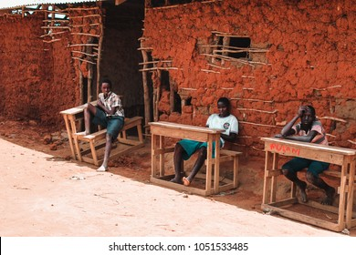 Watamu, Kenya/ Africa - 08/15/2015: African boys on some school desks outside a building constructed of cement and cow dung in Kenya