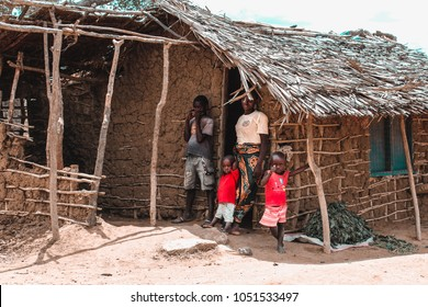 Watamu, Kenya/ Africa - 08/15/2015: A poor African family composed of three children and their mother, put out of their hut made of excrement and cement on the borders of the Savannah