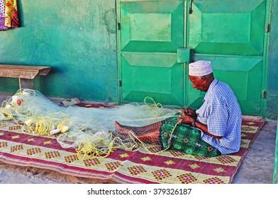 Watamu, Kenya, Africa: a muslim fisherman repairing fishing net in Watamu on February 9, 2010. The main economic sources of the village of Watamu are tourism and fishing