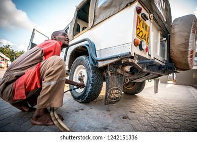 Watamu, Kenya - August 2018: African man mechanic checking wheel's pressure on an off-road vehicle defender.