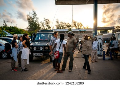 Watamu, Kenya - August 2018: group of tourists and african men ready to go for a safari with off-road vehicles.