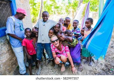 WATAMU, KENYA - January 14, 2017: Female tourist exploring local village. Posing with local children.