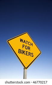 'Watch for Bikers' road warning sign and blue sky. Vertical shot.