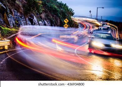 Pass auf Radfahrer auf! Schnellerer Verkehr mit Licht- und Bewegungsunschärfe in der Nähe der Uhr für Radfahrer unterschreiben. Es gibt keinen Fahrradweg. Launceston, Tasmania, Australien.