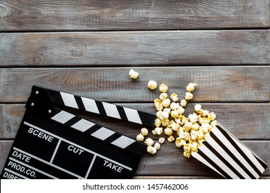 Watch film in cinema with popcorn and clapperboard on wooden background top view