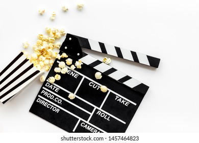 Watch film in cinema with popcorn and clapperboard on white background top view