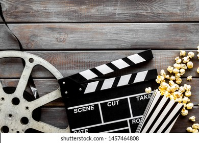 Watch film in cinema with popcorn, video tape and clapperboard on wooden background top view