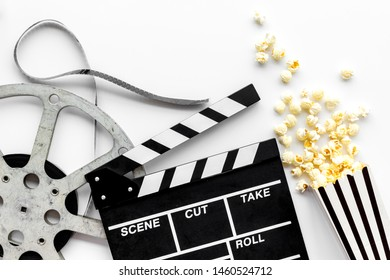 Watch film in cinema with popcorn, video tape and clapperboard on white background top view