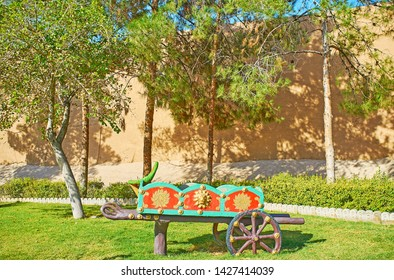 Watch the garden sculpture of old cart in green Mellat park, stretching along Ghal'eh Jalali fortress wall, Kashan, Iran