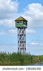 Watch and hunting tower in the Danube Delta with blue sky with clouds and green vegetation close to the river