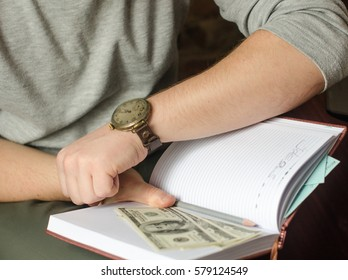 Watch on hand, money, notes, time is money