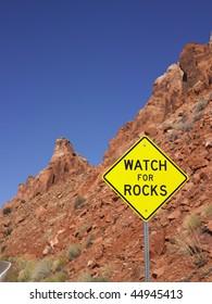 Watch for rocks sign next to highway. Loose rocks on a hillside. Vertical shot.