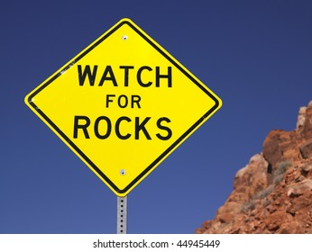 Watch for rocks sign next to highway. Loose rocks on a hillside. Horizontal shot.