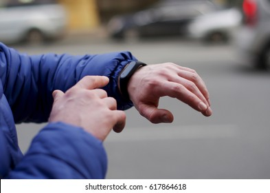 Watch for running on a man's hand on a blurry city background. Close-up black fitness bracelet
