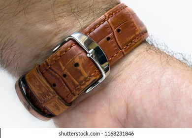 The watch strap is fastened to the wrist of a man. Close-up.