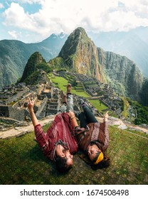 Watch this! Happy young tourist couple are on vacation, with ponchos in Machu Picchu