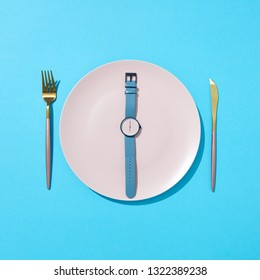 Watch with time six o'clock on a white plate with knife and fork on a blue background, place for text. Concept of limiting the intake of food diet and weight loss. Flat lay.
