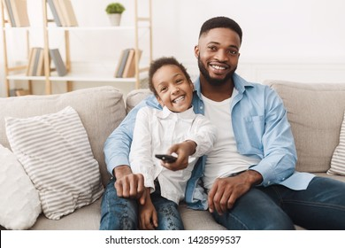 Watch Tv Together. Father And Daughter Switch Channels, Resting On Sofa At Home