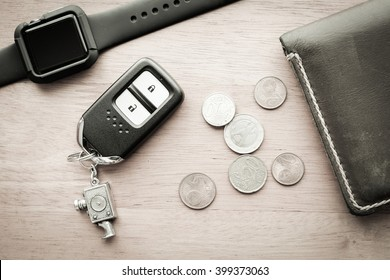Watch with wallet and car remote key on wooden table - vintage filter effect