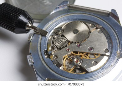 The watch workshop. Repair of old watches. The mechanism of the clock, the screwdriver, which the master makes repairs, is visible. On a white background.