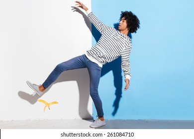Watch your step! Handsome young African man slipping against colorful background