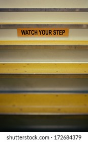 Watch your step sign on stairs leading up