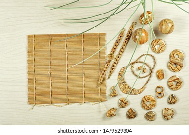 Watches, balls, pendants, bracelets, a necklace made of picture jasper items with bamboo sushi rolling mat on wooden background. Flat lay, top view. Semi-precious stone jewelry concept.