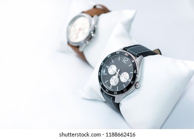 Watches black dial and dark gray stitched watch leather on a white background. Selective focus. Horizontal image.
