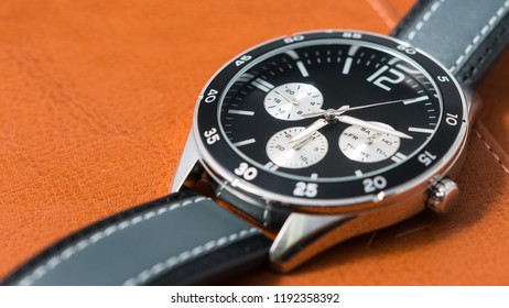 Watches black dial and dark gray stitched watch leather in the vintage style, Close-up, Selective focus. Horizontal image