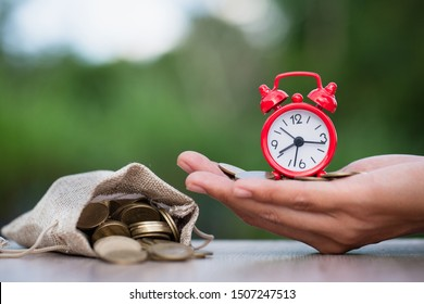Watches and coins placed in the hands of businessmen. Investors nearby have coins poured from a hemp bag. The idea of saving time for retirement planning, long-term investment, saving money.
