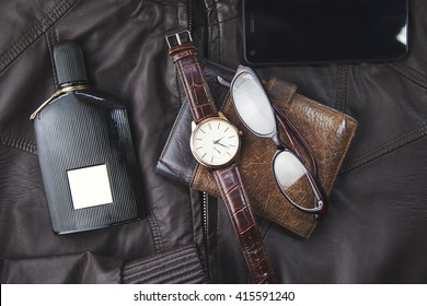 watches,glasses, wallet, perfume  and phone on   leather