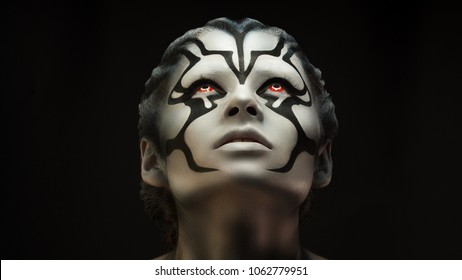 Watchfully looking and  intently looking after.Creative appearance of alien creature with red  eyes and black and white skin is created through a make-up and body-art