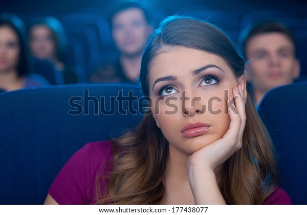 Watching a boring movie. Bored young woman holding hand on chin while watching movie at the cinema
