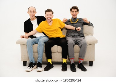 Watching a championship game on tv tree friends sitting on a white sofa isolated on white background. Guy reacts to winning or a lose. Sports tv concept.