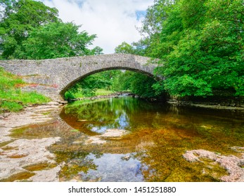 Watching the clear water of the River Ribble pass under an old stone arched bridge in the Yorkshire Dales near Stainforth