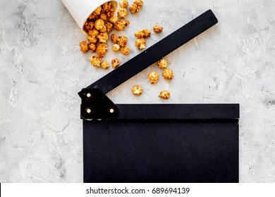 Watching film. Clapperboard and popcorn on grey stone background top view copyspace