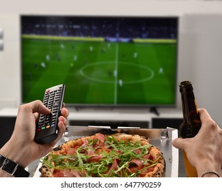 Watching the football game eating pizza,drinking beer holding television control.